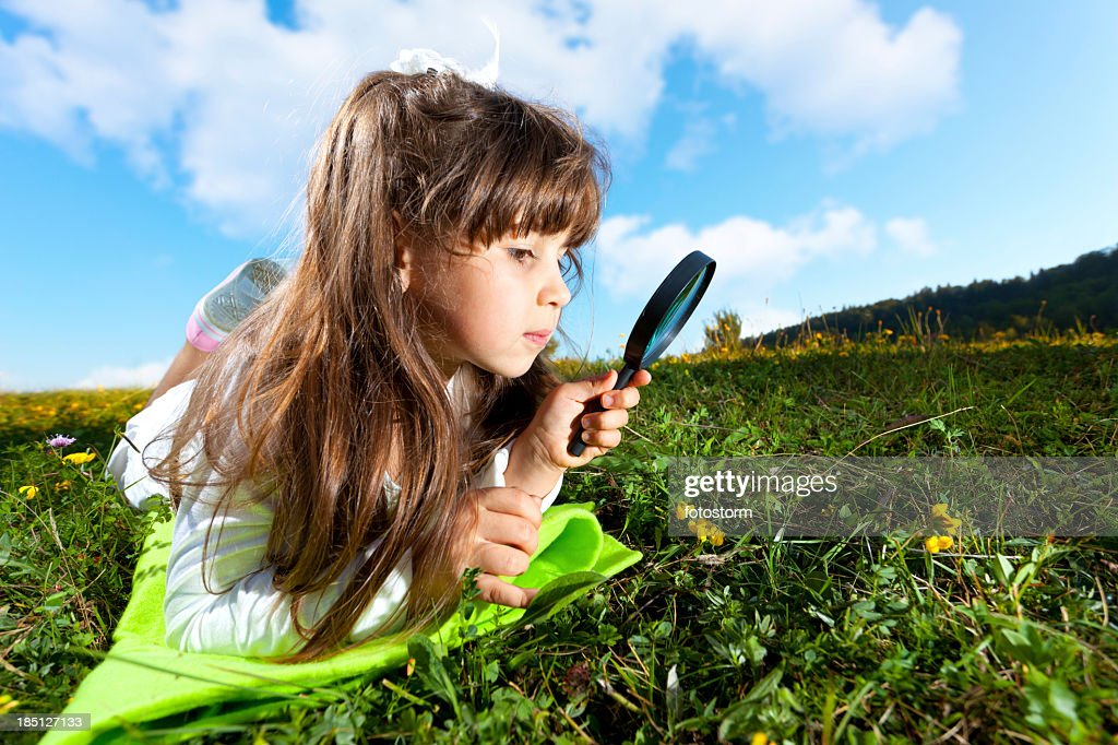 Little Girl Looking Through Magnifying Glass Stock Photo
