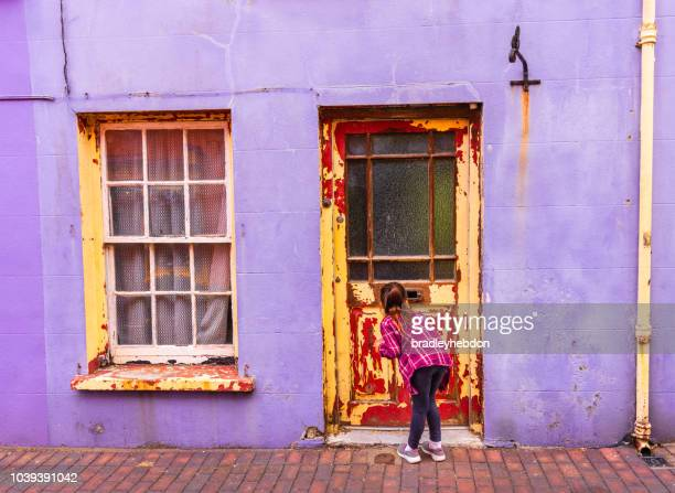 Little girl looking through mail slot of old weathered door in Kinsale, Ireland