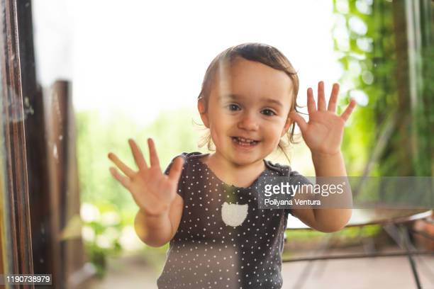 little girl looking through the window - waving gesture stock pictures, royalty-free photos & images