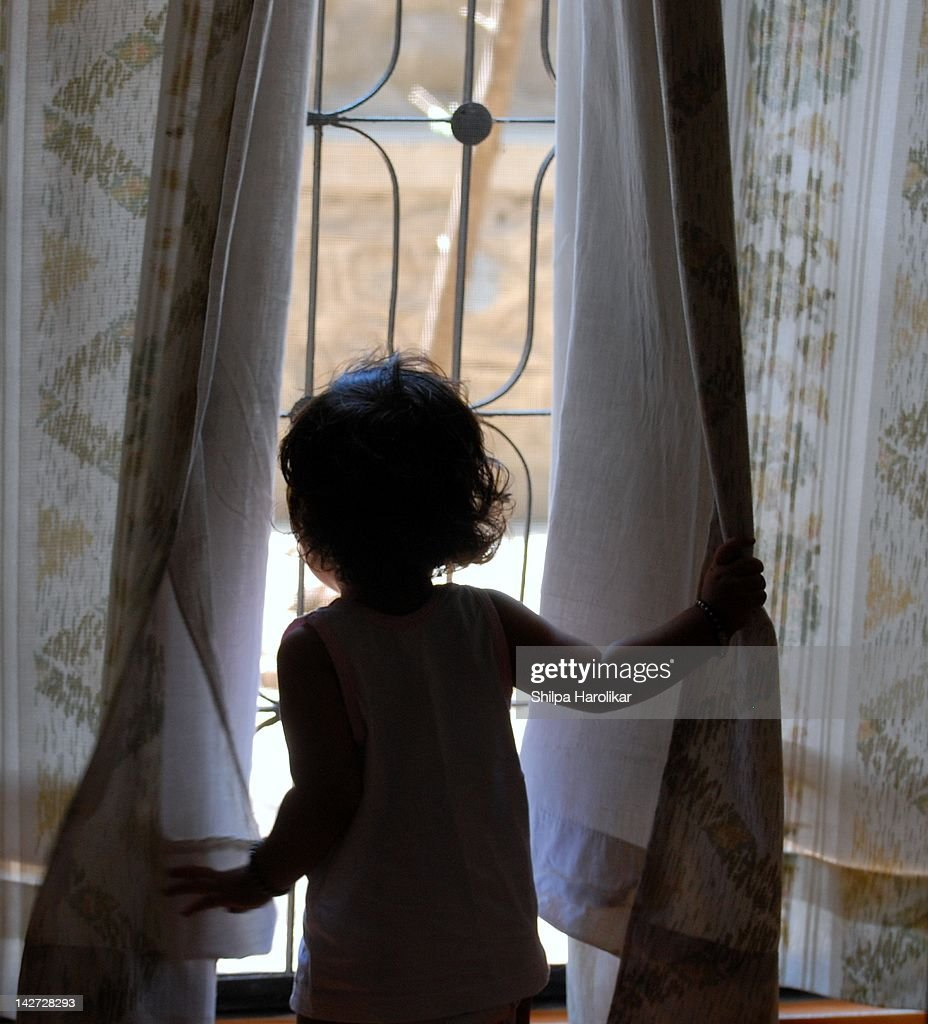 Little girl looking through window : Stock Photo