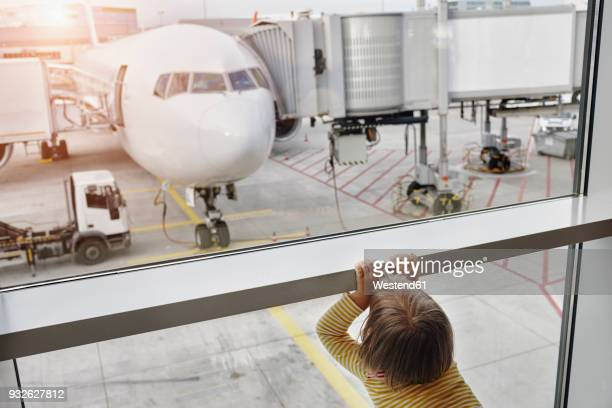 little girl looking through window to airplane on the apron - toddler at airport stock pictures, royalty-free photos & images