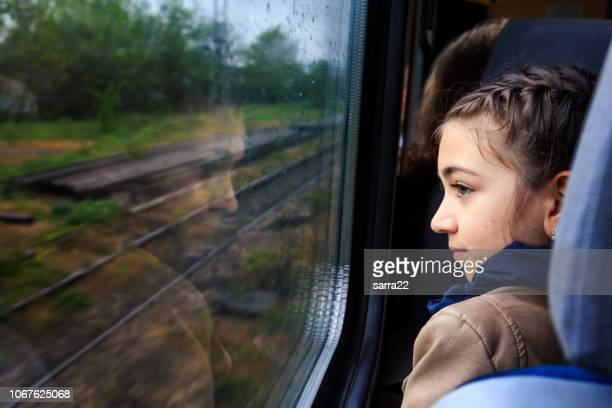 little girl looking through window with reflections. - railroad car stock pictures, royalty-free photos & images