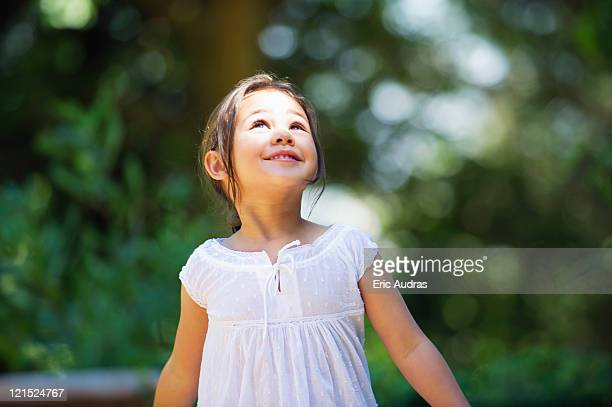 little girl looking up and smiling - solo una bambina femmina foto e immagini stock