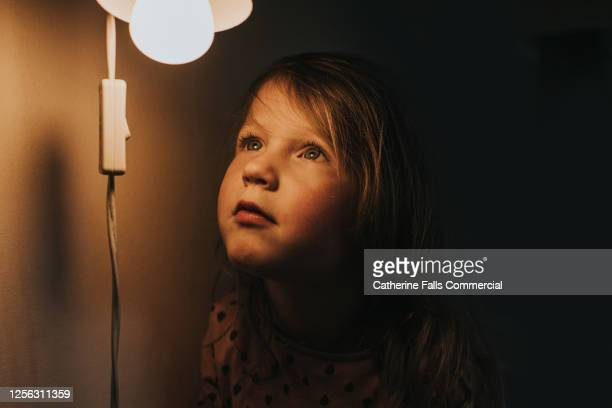 little girl looking up at a small light - lighting equipment stock pictures, royalty-free photos & images