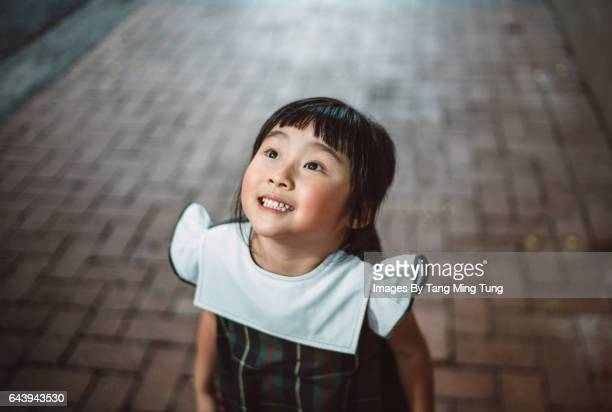 little girl looking up at sky joyfully - curiosity stock pictures, royalty-free photos & images