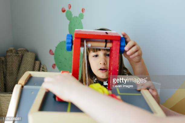 little girl looks in anticipation as she cranks wheel on a wooden toy - calabasas stock pictures, royalty-free photos & images