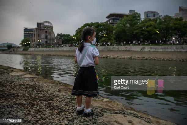 A little girl looks on as lanterns float on the river next to the Atomic Bomb Dome during a ceremony to mark the 75th anniversary of the Hiroshima...