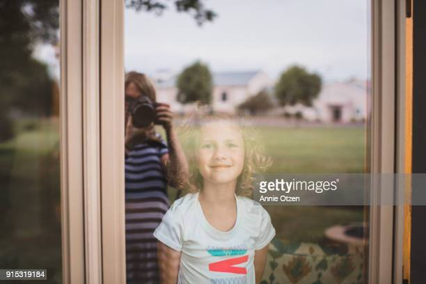 Little Girl Looks Through a window at a photographer