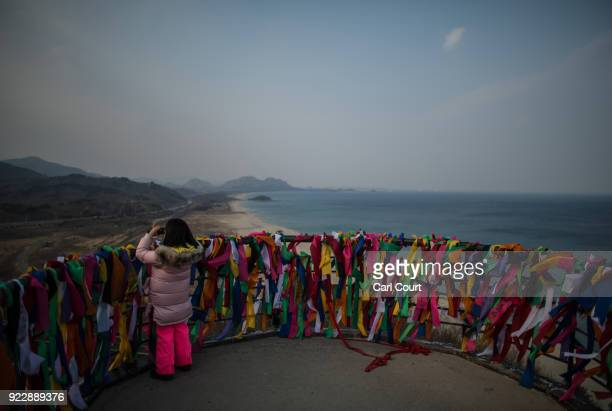 A little girl looks through binoculars towards North Korea from a viewing platform covered with ribbons bearing goodwill messages during a visit to...
