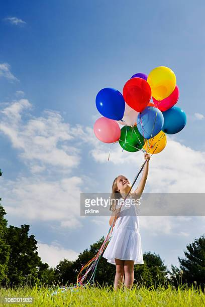 Little girl looks up at balloons held aloft