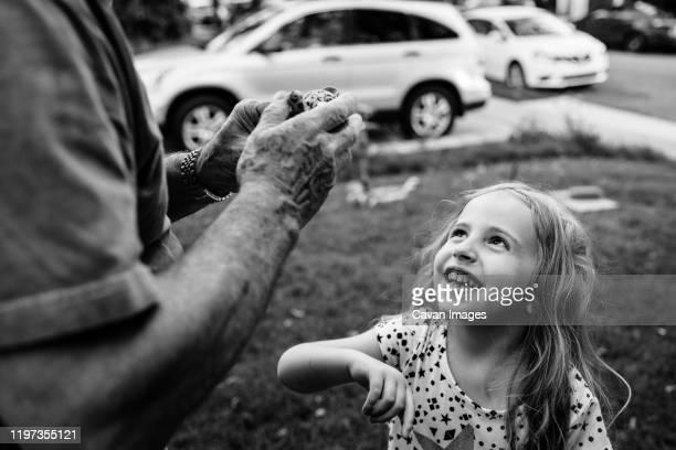 a little girl looks up at her grandfather. - schwarzweiß bild stock-fotos und bilder