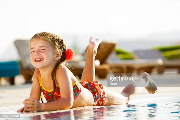 little girl lying by edge of pool on sunny day - kids pool games stock pictures, royalty-free photos & images