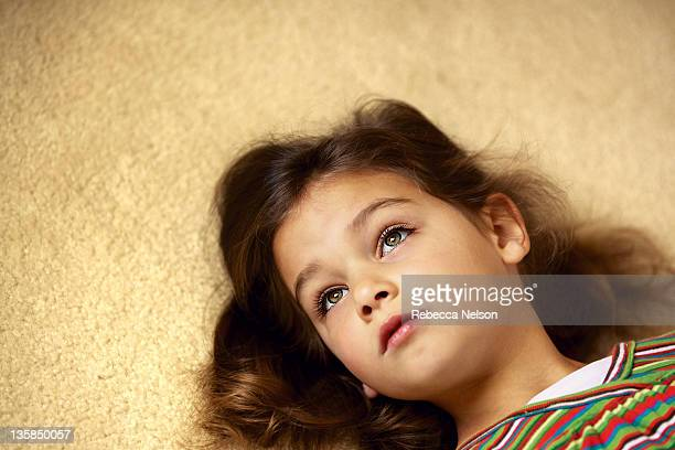 little girl lying carpeted floor - rebecca nelson stock pictures, royalty-free photos & images