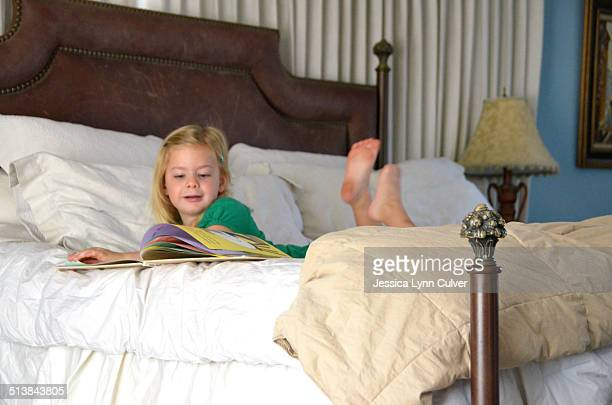 little girl lying on a bed looking at books - barefoot feet up lying down girl stock photos and pictures