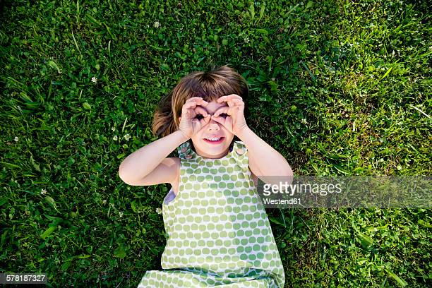 Little girl lying on a meadow looking through her fingers