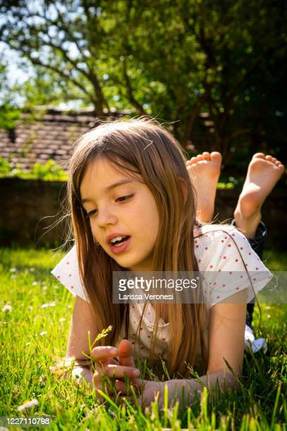 little girl lying on a meadow - larissa veronesi stock-fotos und bilder