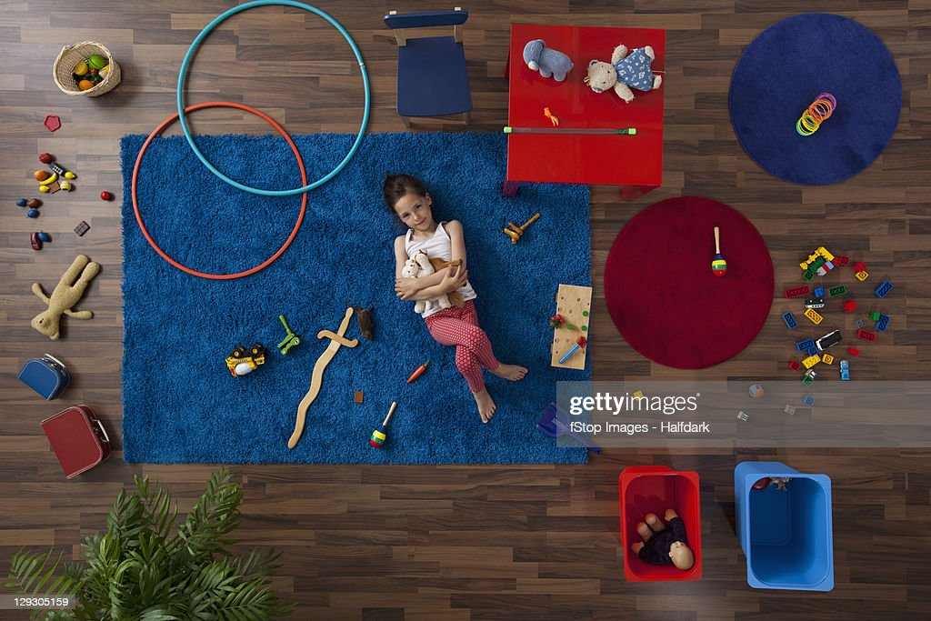 A little girl lying on a rug hugging stuffed animals, overhead view : Stock Photo