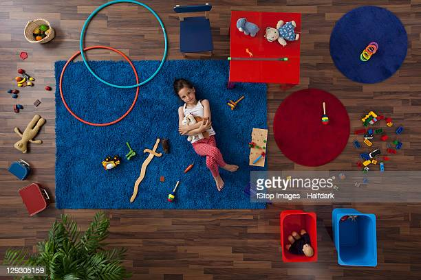 A little girl lying on a rug hugging stuffed animals, overhead view