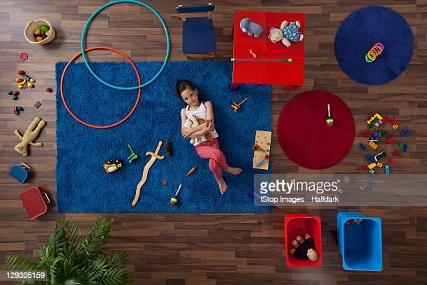 a little girl lying on a rug hugging stuffed animals, overhead view - grote groep dingen stockfoto's en -beelden