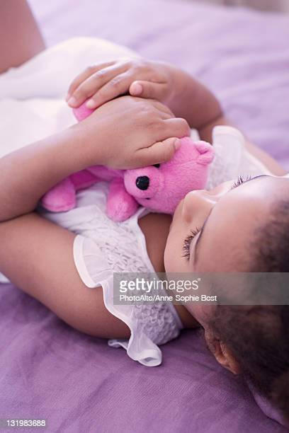 Little girl lying on bed with teddy bear