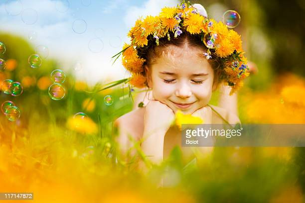 Kleines Mädchen auf dem Bauch liegen Löwenzahn-Feld