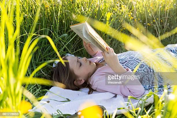 Little girl lying on field of flowers reading a book