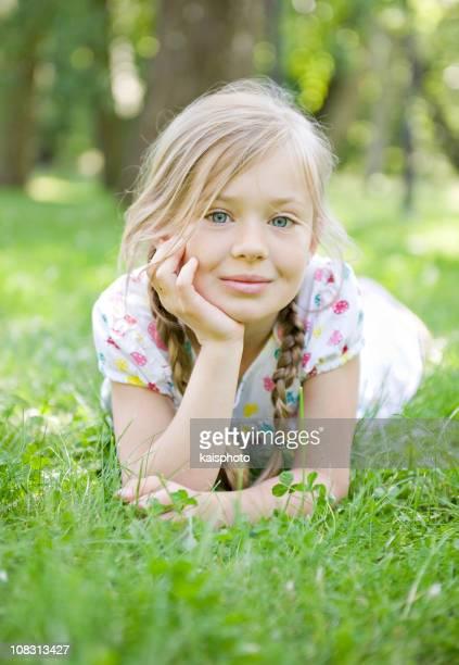 Kleines Mädchen am Gras liegen