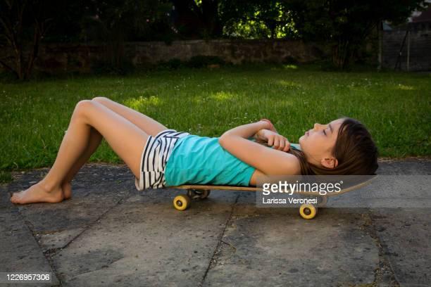 little girl lying on her skateboard, eyes closed - larissa veronesi stock-fotos und bilder