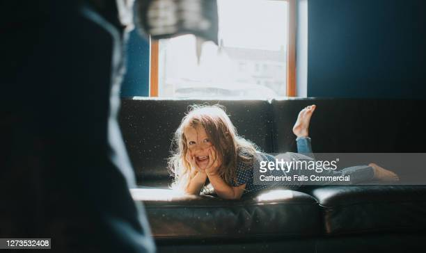 little girl lying on her stomach on a sofa - sofa stock pictures, royalty-free photos & images