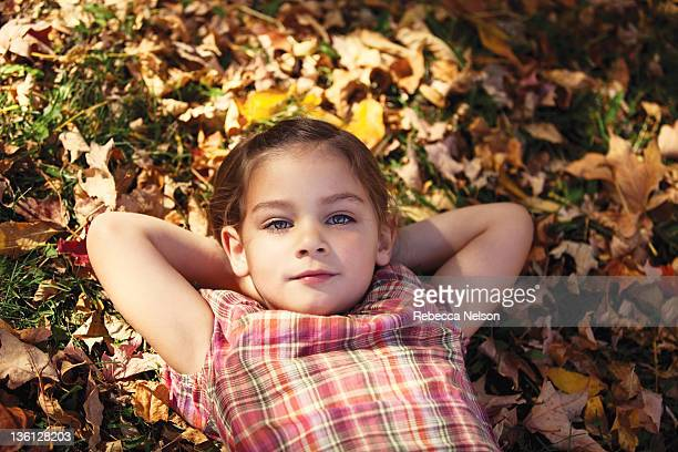 little girl lying on leaf strewn ground - rebecca nelson stock pictures, royalty-free photos & images