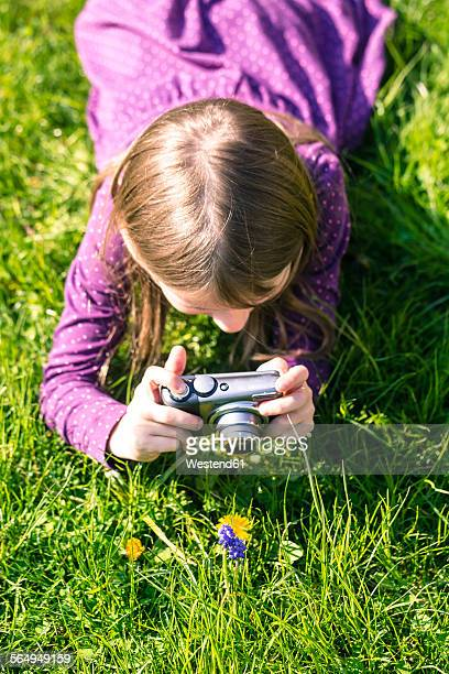 Little girl lying on meadow photographing a flower