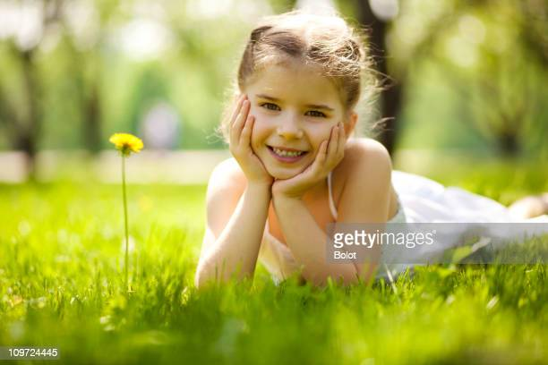 Little girl lying on the grass and looking at the camera