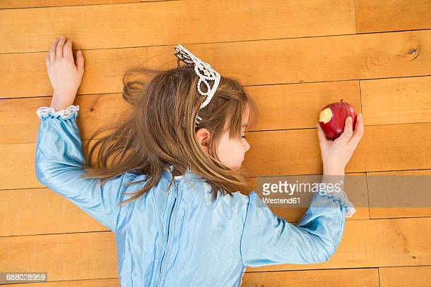 little girl lying on wooden floor holding bitten red apple - fainting stock pictures, royalty-free photos & images