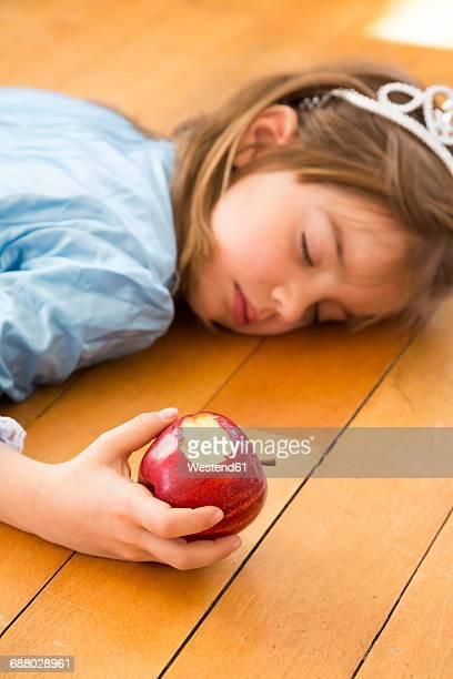 Little girl lying on wooden floor holding bitten red apple