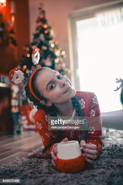 Petite fille couché sous l'arbre de Noël et de boire des boissons chaudes