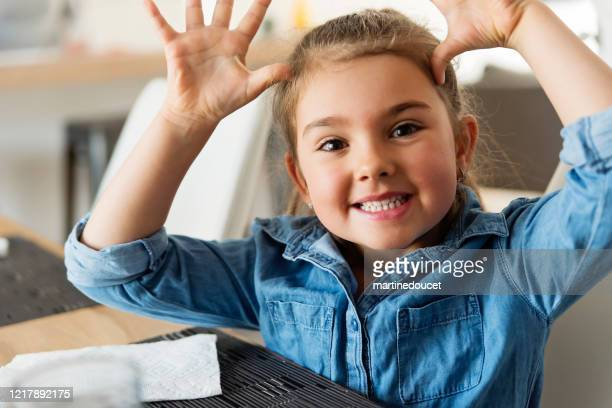 """little girl making a funny face waiting for her plate at lunch time. - """"martine doucet"""" or martinedoucet stock pictures, royalty-free photos & images"""