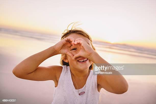 Kleine Mädchen machen ein Herz am Strand