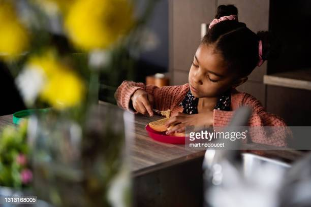 """little girl making a peanut butter toast for snack. - """"martine doucet"""" or martinedoucet stock pictures, royalty-free photos & images"""