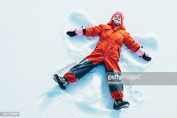 little girl making a snow angel - mitten stock pictures, royalty-free photos & images