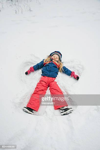 Little girl making a snow angel