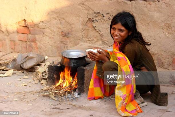 little girl making and drinking tea - punjab pakistan stock photos and pictures