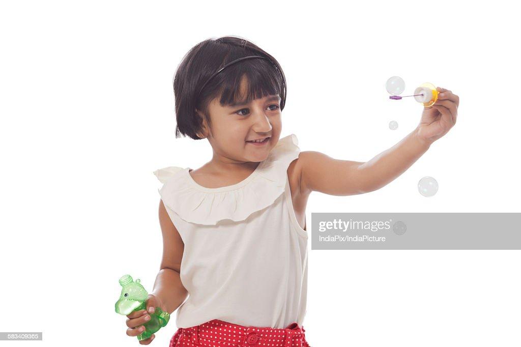 Little girl making bubbles : Stock Photo