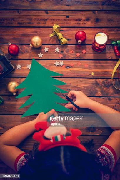 Kleine Mädchen machen Weihnachtskarte