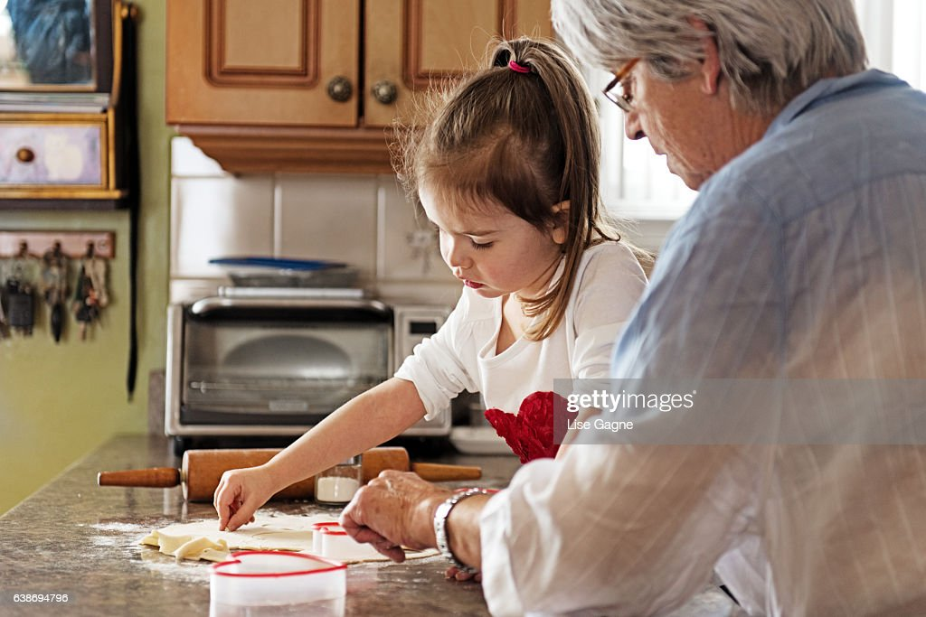Little girl making cookies with grandma : Stock Photo