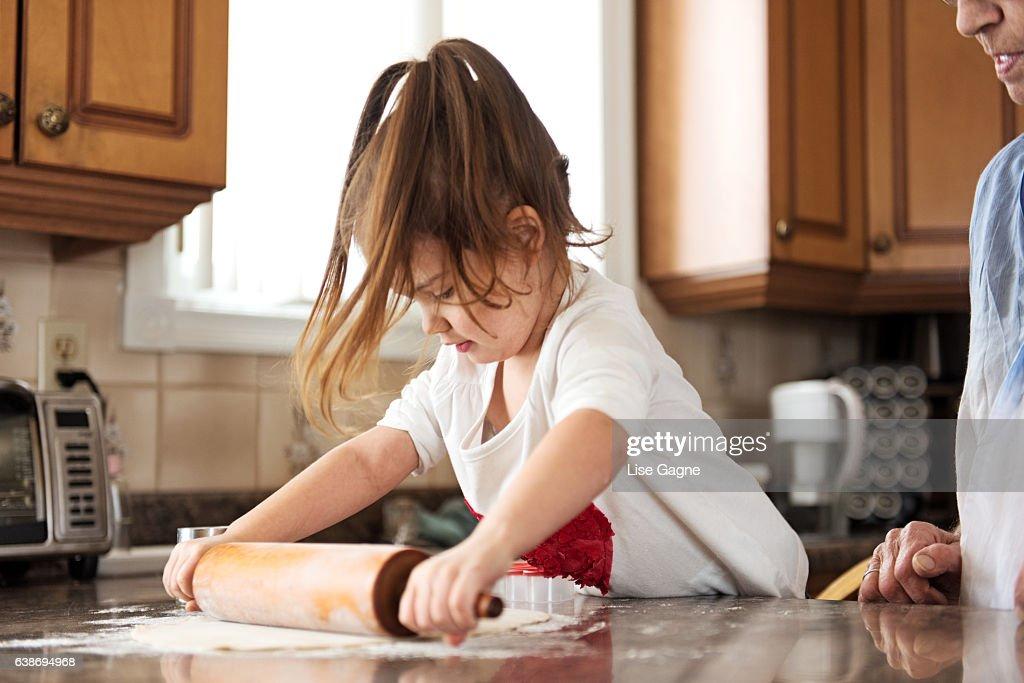 Little girl making cookies with grandma : Foto de stock
