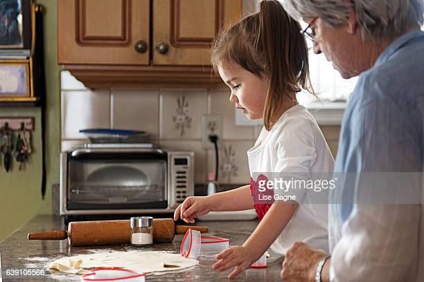Little girl making cookies with grandma