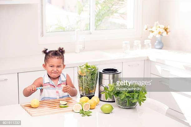 Little girl making face. Sour taste of lemon.