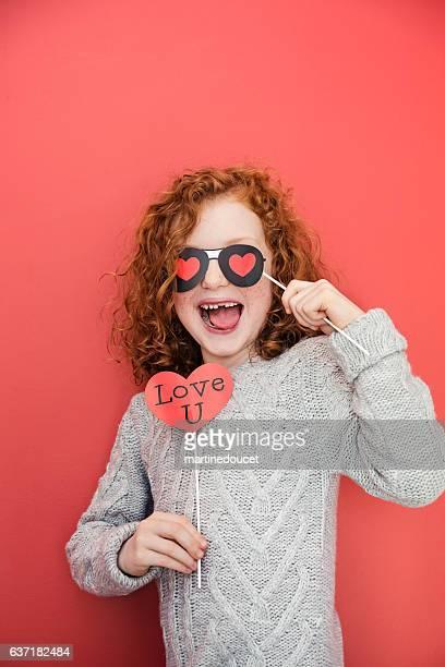 """赤い壁に小道具で顔を作る小さな女の子。 - """"martine doucet"""" or martinedoucet ストックフォトと画像"""