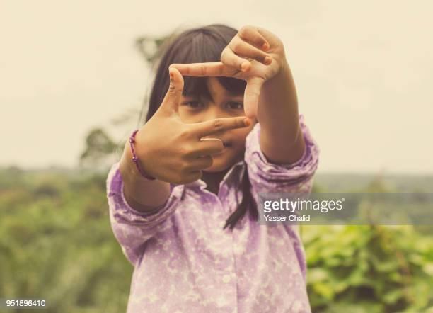 little girl making finger frame - dedos fazendo moldura - fotografias e filmes do acervo