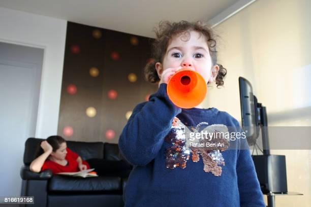 little girl making noise at home while her mother is relaxing - rafael ben ari bildbanksfoton och bilder